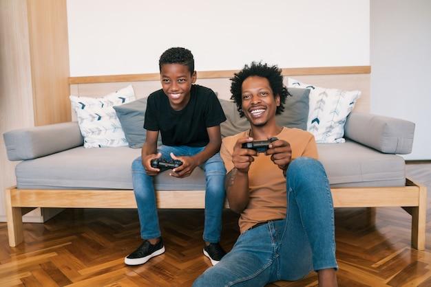 Vader en zoon spelen van videospellen samen thuis.