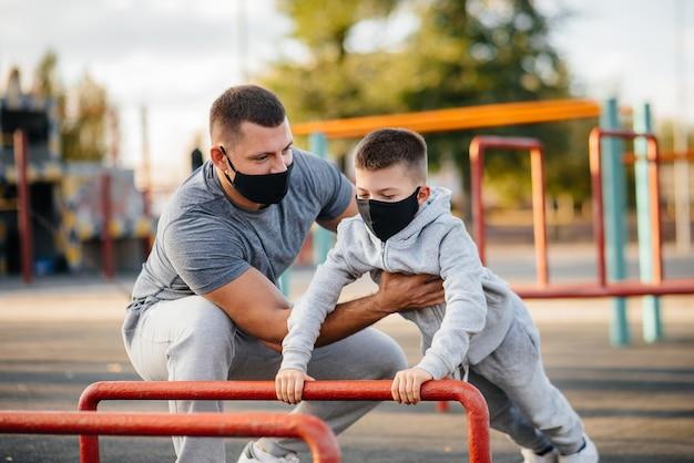 Vader en zoon sporten in maskers op het sportveld