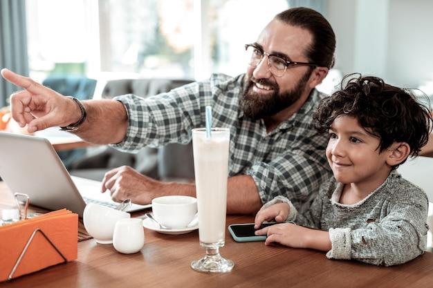Vader en zoon. stralende lachende vader en zoon kijken naar hun moeder die naar het restaurant komt