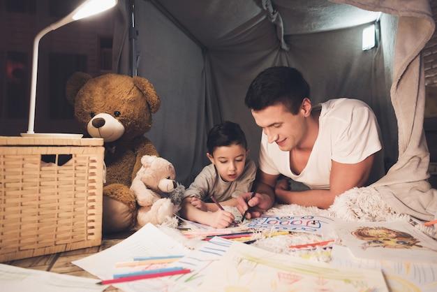 Vader en zoon tekenen met kleurpotloden op papier.