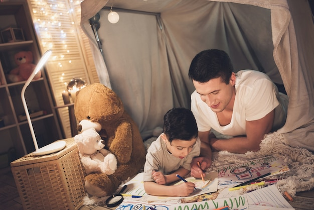Vader en zoon tekenen 's nachts met kleurpotloden.