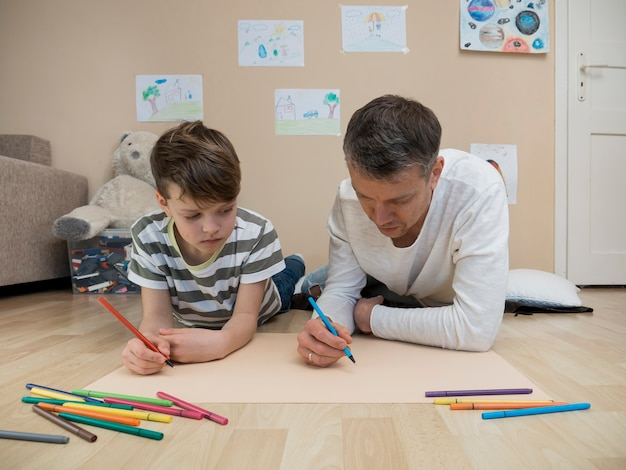 Vader en zoon tekenen samen op de vloer