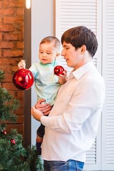 Vader en zoon versieren kerstboom in de woonkamer
