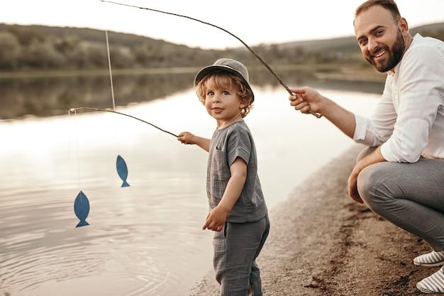 Vader en zoon vissen op de oever van het meer