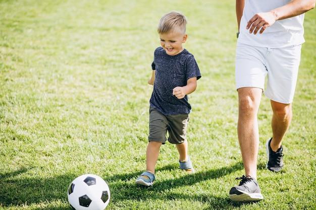 Vader en zoon voetballen bij het veld