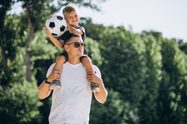 Vader en zoon voetballen op het strand