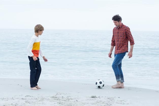 Vader en zoon voetballen op zee kust