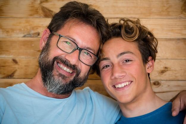 Vader en zoon vrolijk portret met houten achtergrond - gelukkige blanke volwassen en jonge mannelijke familie die op camera kijkt