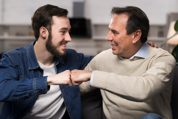 Vader en zoon vuist stoten in de woonkamer