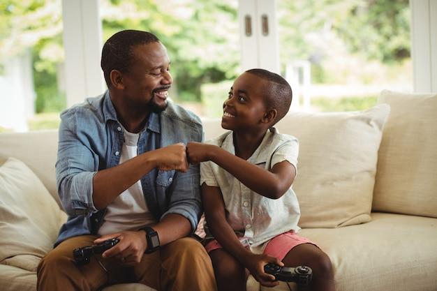Vader en zoon vuist stoten tijdens het spelen van video game