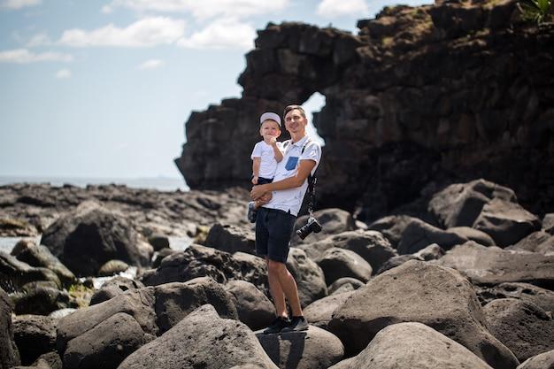 Vader en zoon wandelen langs de oever van de oceaan. weekend aan het strand. een strandsteen.
