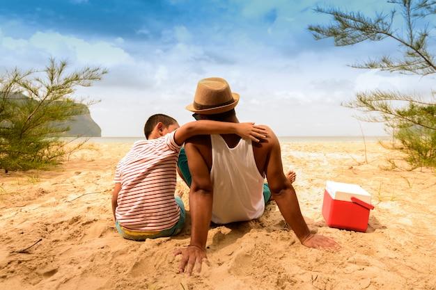 Vader en zoon zijn blij met picknick met uitzicht op zee.