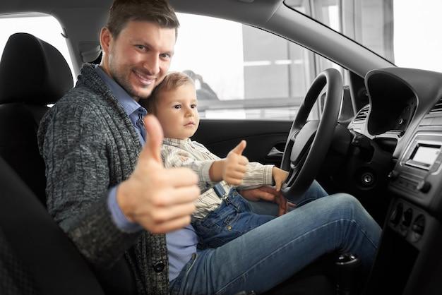 Vader en zoon zitten in de auto cabine, duimen opdagen.