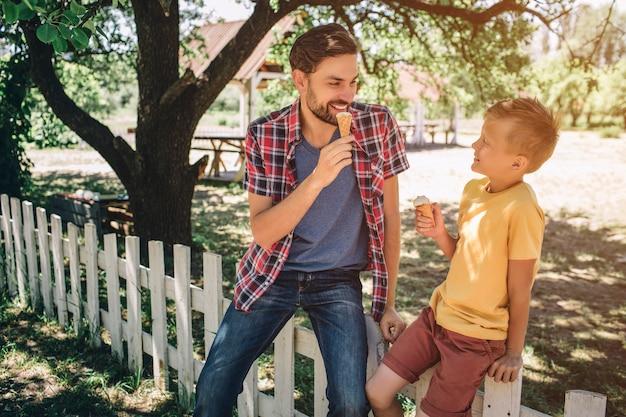 Vader en zoon zitten op wit hek en kijken naar elkaar. ze eten ijs. ook glimlachen ze naar elkaar.