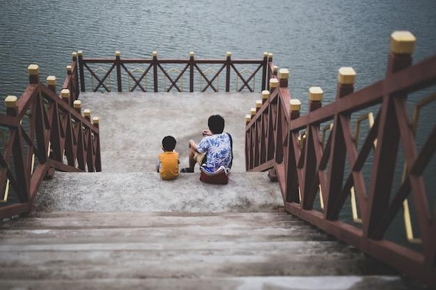 Vader en zoon zitten samen op brug bij het meer