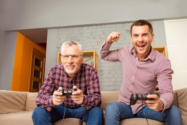 Vader en zoon zittend op de bank en spelen van videospellen