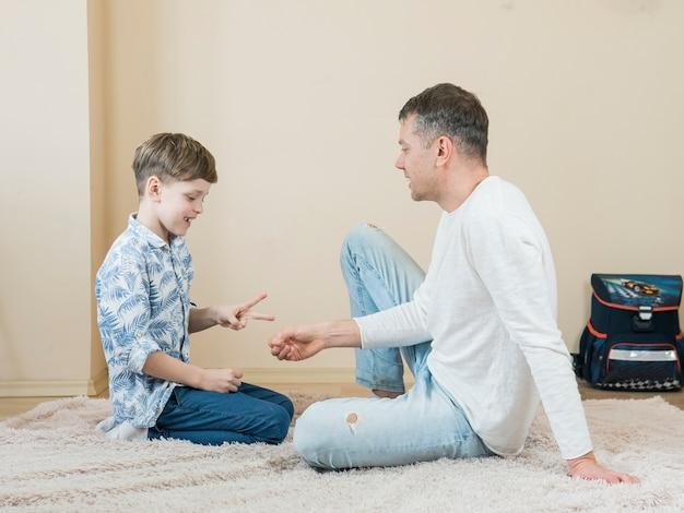 Vader en zoon zittend op de vloer
