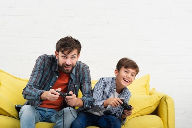 Vader en zoon zittend op een bank en spelen op console