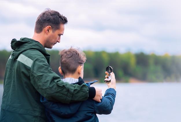 Vader en zoon zoeken naar de juiste richting met behulp van een kompas op de rivieroever