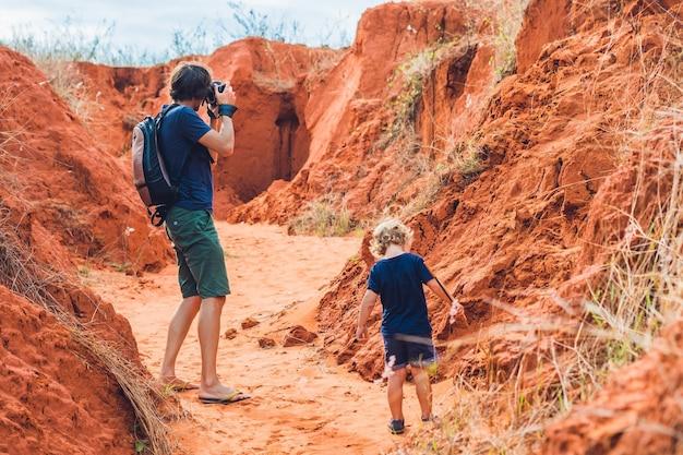 Vader en zoonreizigers in rode kloof dichtbij mui ne, zuidelijk vietnam. reizen met kinderen concept.