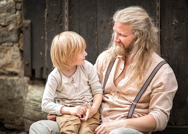 Vader en zoonsclose-up tegen een donkere houten muur. een jongen en een man praten. portret van mensen