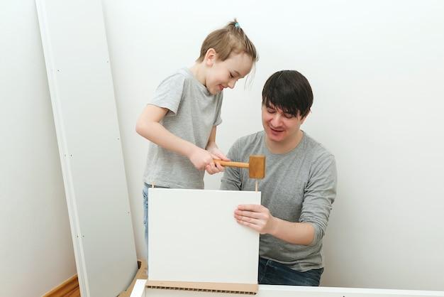 Vader en zoontje die thuis meubels monteren. meubelmontage zelf. vader helpt zijn zoon om een boekenplank in elkaar te zetten. vaderschap, relatie en familieconcept.