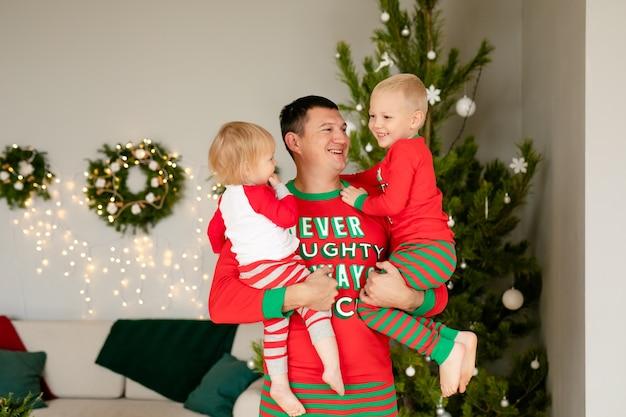 Vader en zoontje en dochter in gezellige pyjama's die cadeaus uitpakken