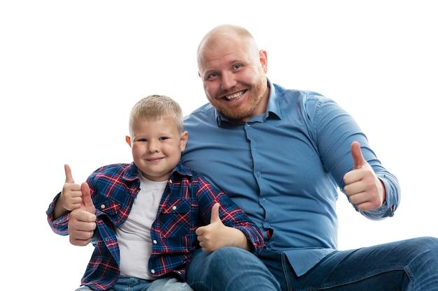 Vader en zoontje glimlachen en knuffelen. liefde en tederheid in een relatie. geïsoleerd
