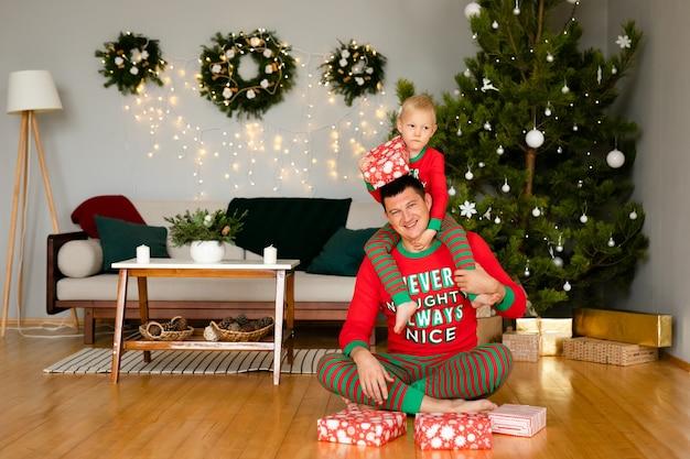 Vader en zoontje in knusse pyjama geschenken uitpakken