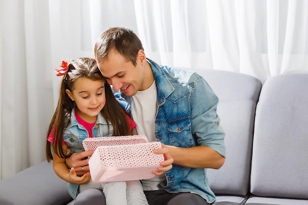 Vader geeft dochter een kerstcadeau in de woonkamer