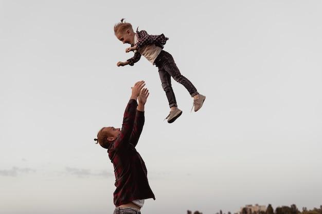 Vader geeft zijn kind over. vakantie met het gezin. een blije familie. gelach en vreugde van kinderen.
