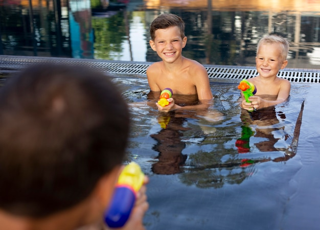 Vader geniet van een dagje met zijn kinderen aan het zwembad Premium Foto