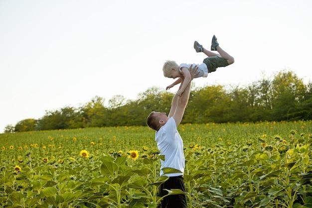 Vader gooit zijn zoontje op een groen veld met zonnebloemen