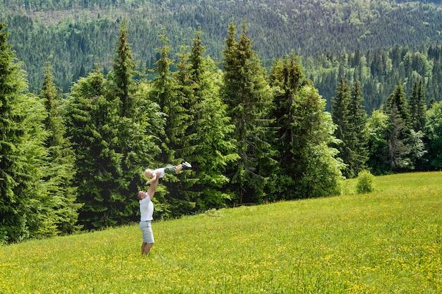 Vader gooit zoontje in de groene weide op een muur van groene dennenbossen.