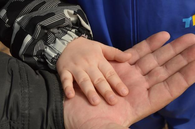 Vader, grootvader, houdt het handvat van een klein kind in mijn hand