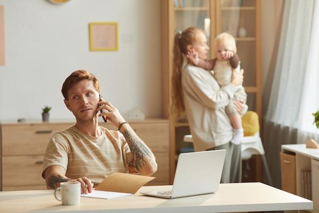 Vader heeft een gesprek op de mobiele telefoon terwijl hij aan tafel zit met zijn vrouw en baby in de kamer