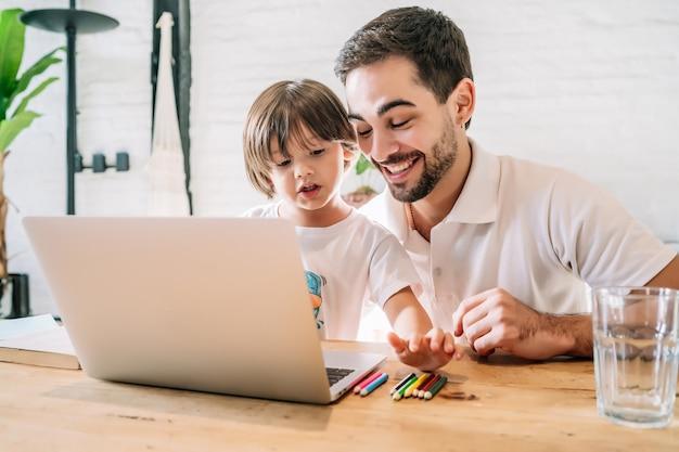 Vader helpt en ondersteunt zijn zoon met online school terwijl hij thuis blijft. nieuw normaal levensstijlconcept.