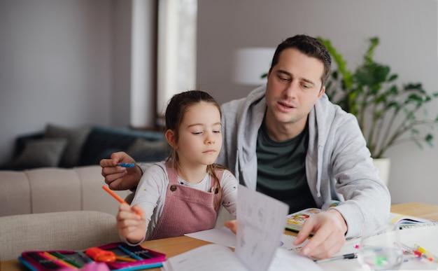 Vader helpt kleine dochter met huiswerk binnenshuis, afstandsonderwijs.