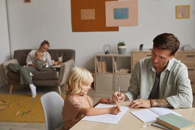 Vader helpt zijn zoon om zijn huiswerk aan tafel te doen met moeder die met zoontje speelt