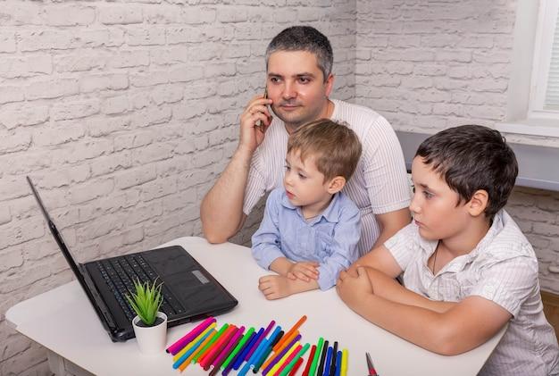 Vader helpt zijn zoons bij online huiswerk