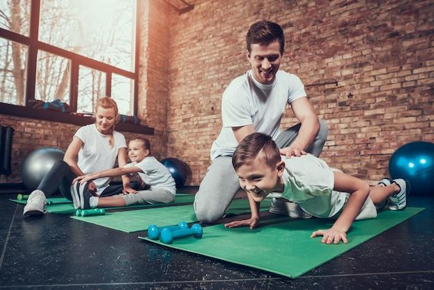 Vader helpt zoon met push-ups. moeder stretch dochter.