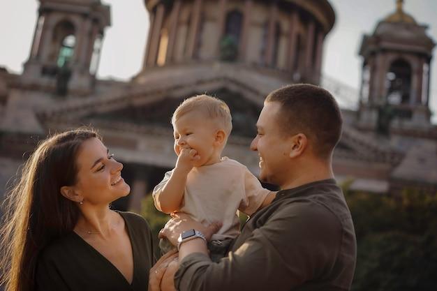 Vader houdt babyjongen vast, moeder staat dicht bij hen glimlachend en kijkt vrolijk naar hun zoon