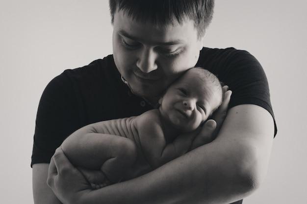 Vader houdt de baby in zijn armen. opvoeding van de vader van jonge kinderen, gelukkige jeugd, een vriendelijk gezin.
