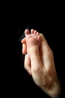 Vader houdt de kleine voet van zijn pasgeboren zoon vast.