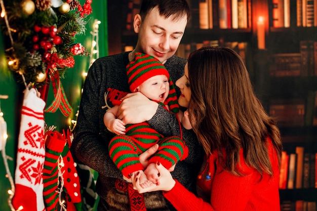 Vader houdt kind in gestript pak staande voor een kerstboom, terwijl moeder met haar speelt