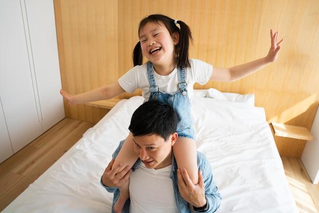 Vader houdt meisje op schouders