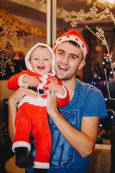 Vader houdt op zijn handen een kleine jongen verkleed als kerstman
