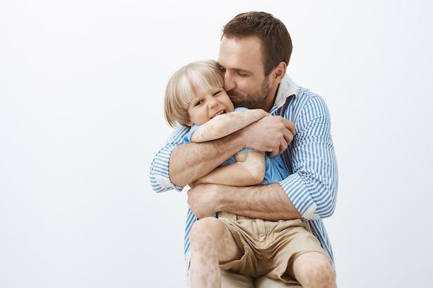 Vader houdt van zijn zoontje als geen ander. leuke, goed uitziende, zorgzame vader die kind knuffelt en kust op de wang, zich gelukkig voelt door tijd door te brengen met kind, staande over grijze muur