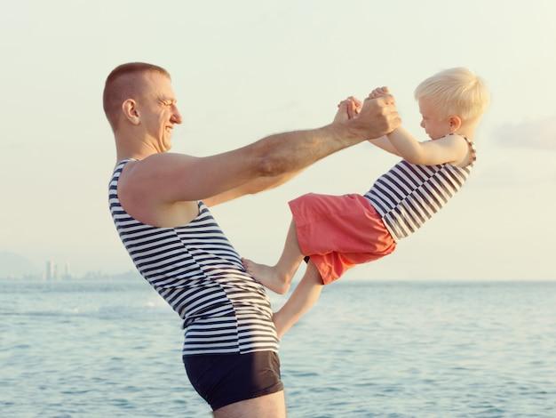 Vader houdt zijn zoon in uitgestrekte handen op de zeekust. veel plezier