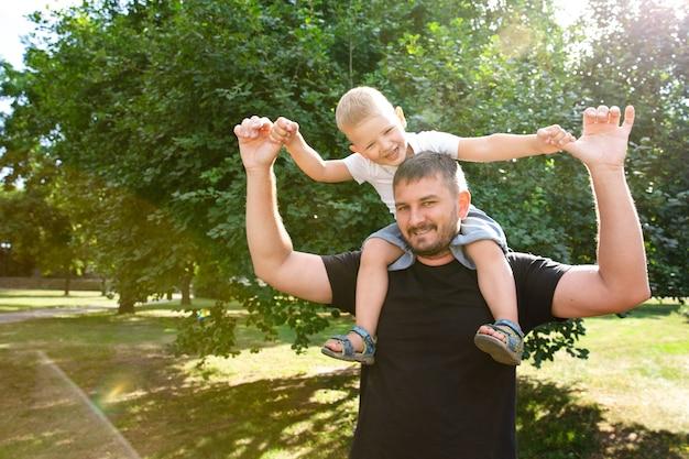 Vader houdt zijn zoon op zijn rug als een vliegtuig in park buiten